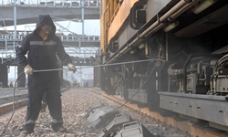 Rail grinding workers stick to posts outdoors in Zhengzhou